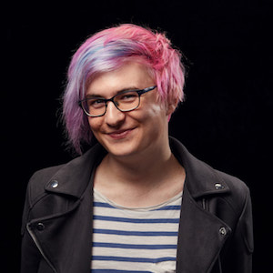 A photo of me! A woman with pink and blue hair, wearing a stripy t-shirt and a suede jacket.